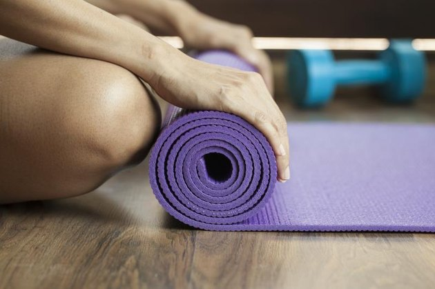 A woman unrolls an exercise or yoga mat.