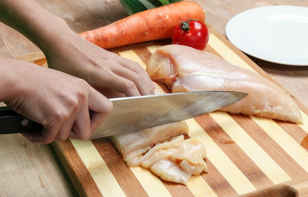 woman's hand cutting chicken breast