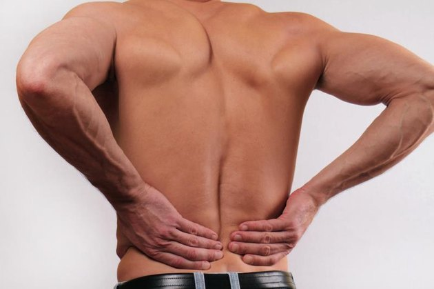 Close up of man holding his lower back. Man rubbing his painful back. Pain relief concept