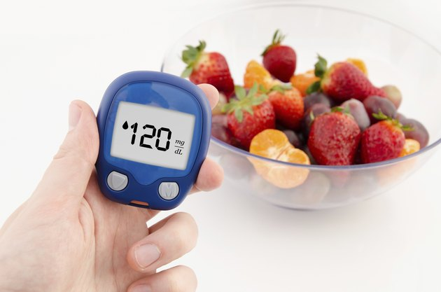 Hand holding meter. Diabetes doing glucose level test. Fruits in