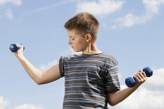 Happy boy lifting dumbbells outdoors