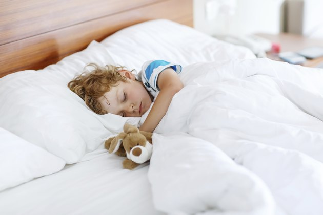 Adorable kid boy after sleeping in white bed with toy