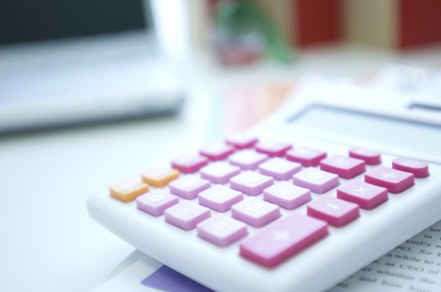 Pink calculator on desk with laptop