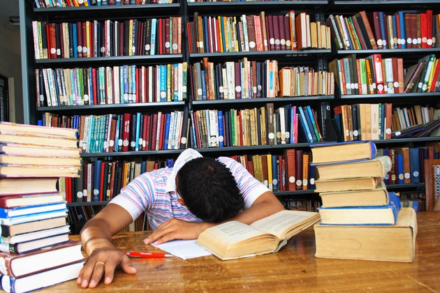 Close up of a young boy with his head down in the library