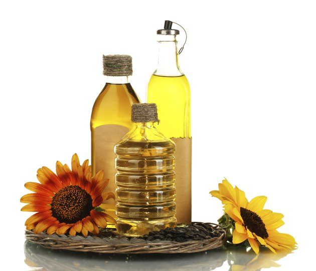 oil in bottles, sunflowers and seeds isolated on white