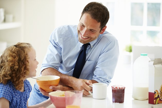 Father And Daughter Having Breakfast In Kitchen Together