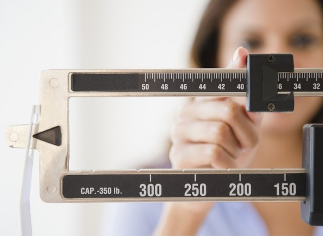 Cape Verdean woman weighing herself