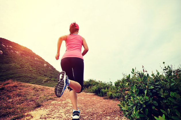 runner running on seaside mountain trail