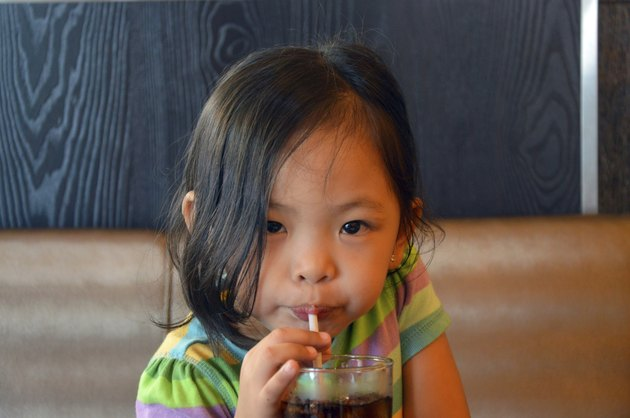 child sipping soda