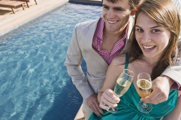 Couple with champagne poolside