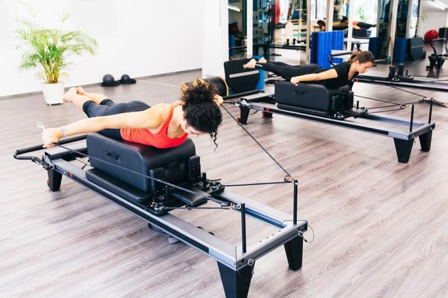 Women stretching on reformer beds