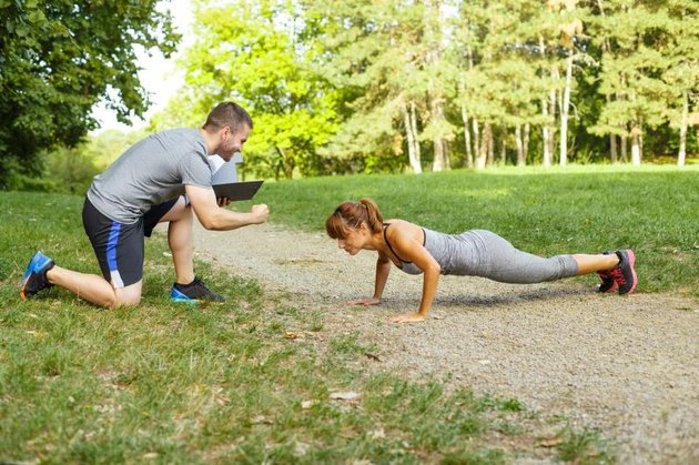 Man trainer motivates women to do push-ups