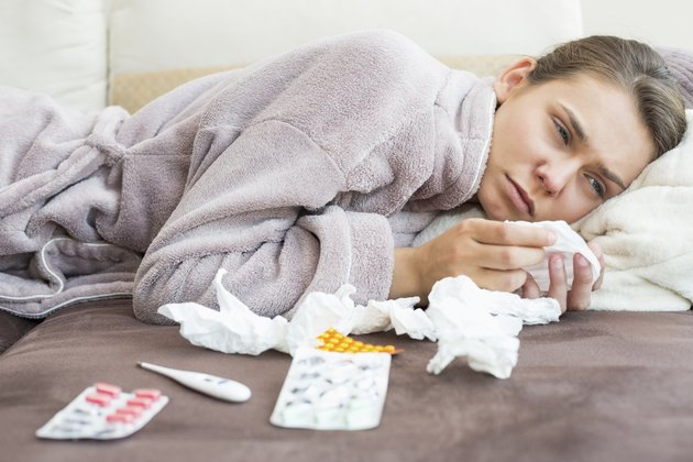 Sad woman with tissue and medicines lying on bed