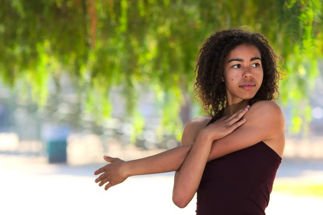 Young woman with curly hair stretching outside