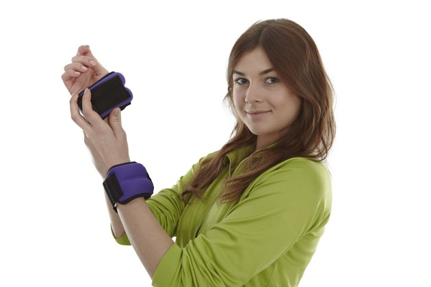 Girl with wrist weights, isolated on white.
