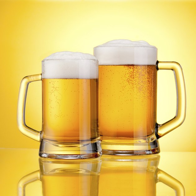 Two Mugs beer with cap of foam on yellow