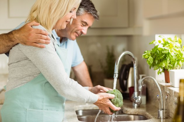 Happy mature couple washing broccoli