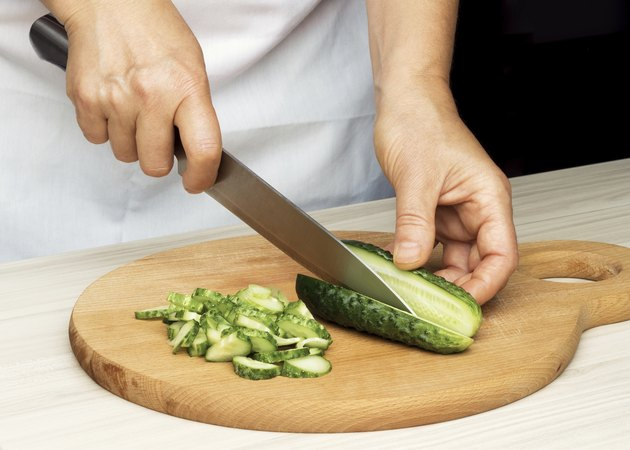 Woman's hand slicing a cucumber.
