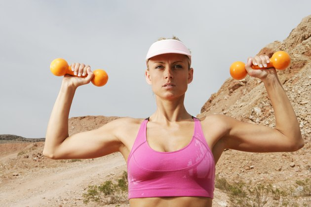 Woman working out with hand weights outdoors