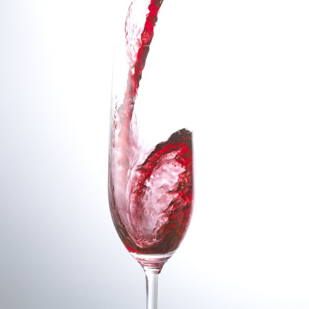 Red Wine Being Poured Into a Champagne Flute