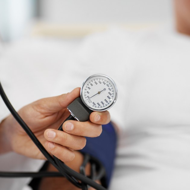 Close-up of doctor taking blood pressure of patient