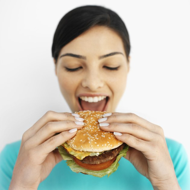 Front view portrait of young woman eating burger