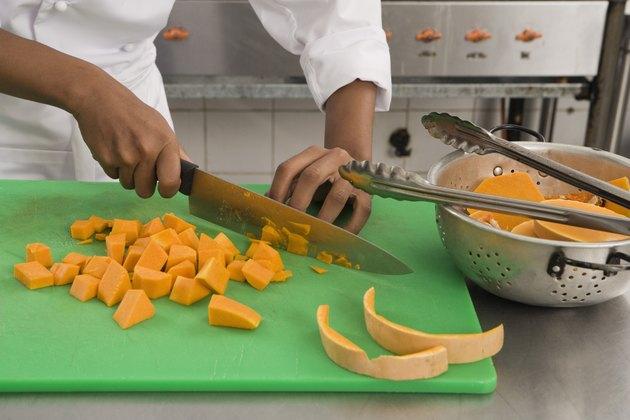 Chef cutting squash in kitchen