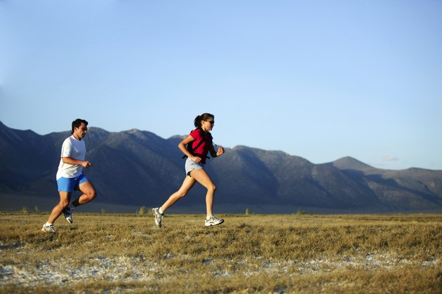 Man and woman running with mountains,  California,  USA