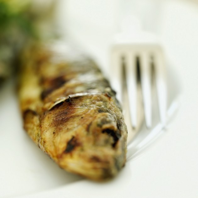 Close-up of a whole fried fish with a knife