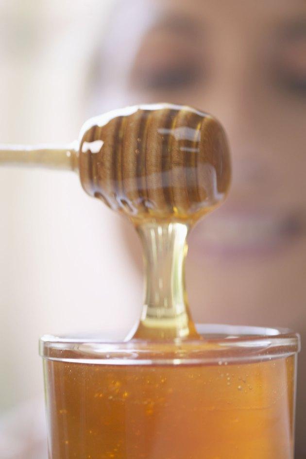 Fresh honey dripping from dipper