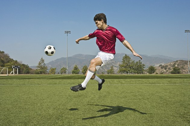 Jumping soccer player kicking ball