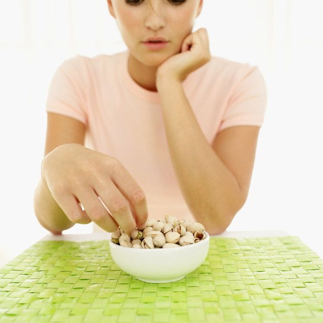 Young woman picking nuts from bowl