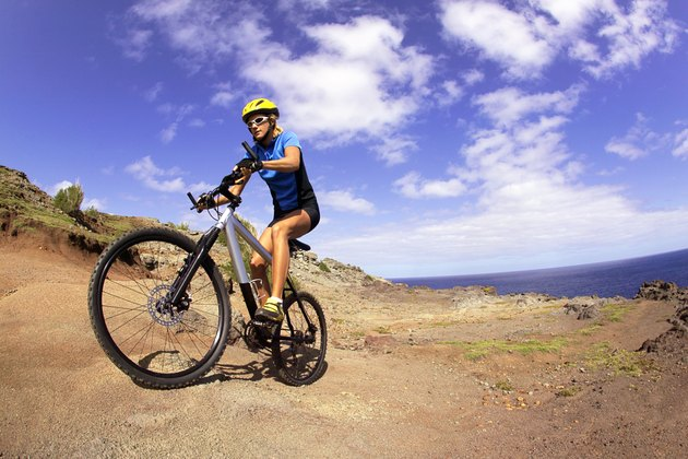 Low angle of a woman riding her bicycle on a dirt road near a rocky coastal cliff.