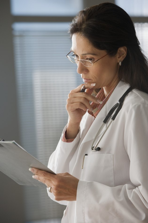 Female doctor examining clipboard