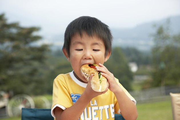 Japanese boy eating a sandwich