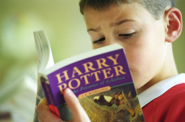 """A young boy reads """"Harry Potter and the Prisoner of Azkaban"""" by J.K. Rowling in a book shop in Shirley, Birmingham, U.K."""