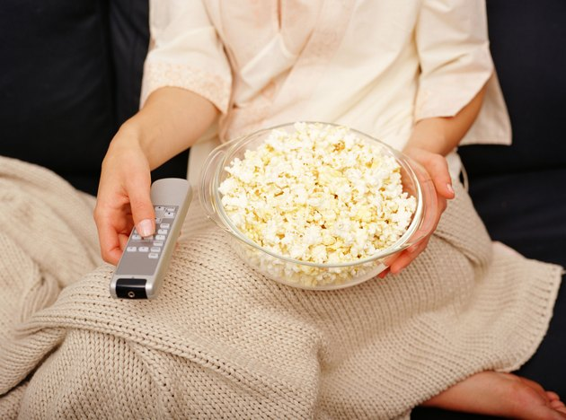 Person holding popcorn and remote control