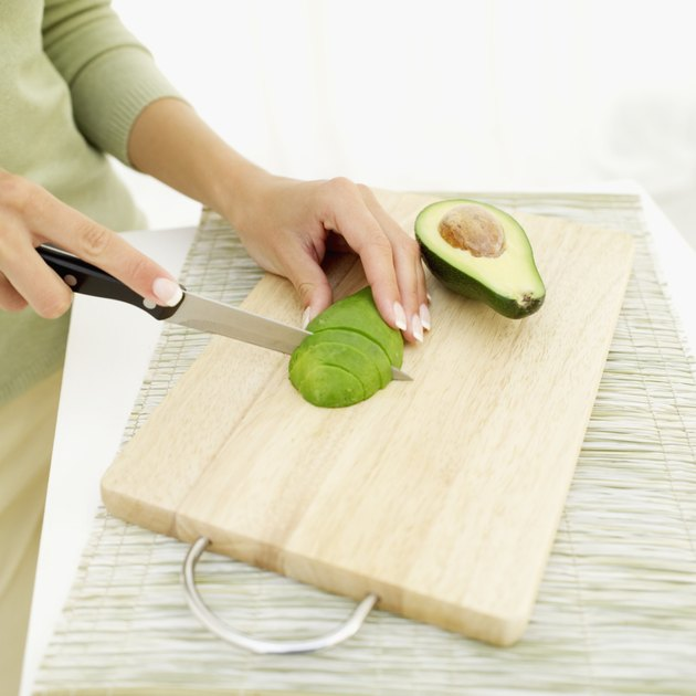 Young woman slicing an avocado with a knife
