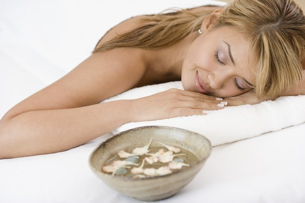 Hispanic woman laying on spa table
