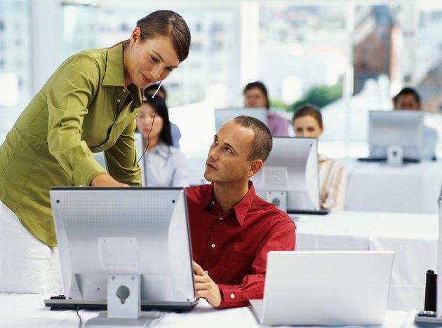 businesswoman training a businessman at a seminar