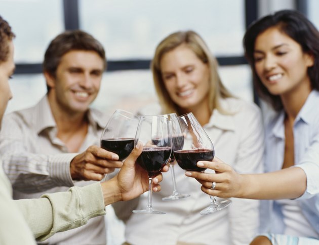four people toasting with red wine