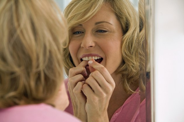 Mid adult woman flossing her teeth