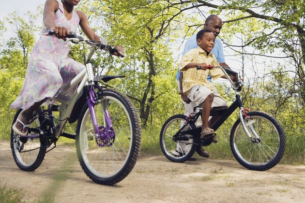 African grandfather teaching grandson to ride a bicycle in park