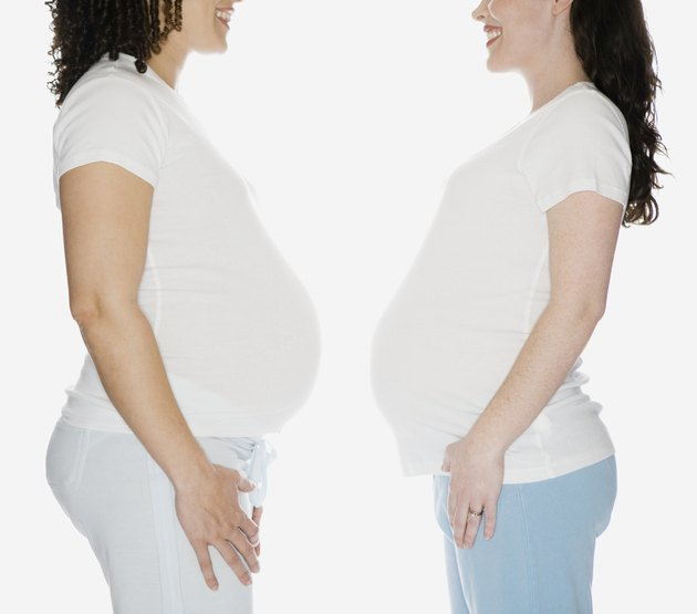 Multi-ethnic pregnant women facing each other