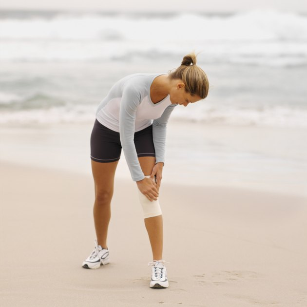 Front view of a concerned woman wearing a knee support holding her knee