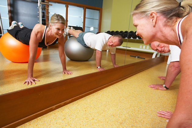 Couple exercising by mirror at gym