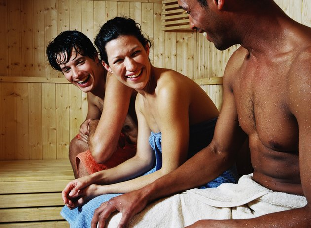 group of young people sitting in sauna smiling