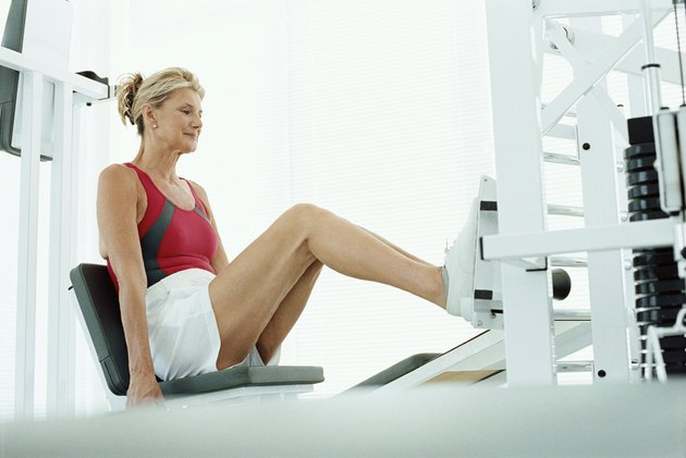 Senior woman using leg press machine in a gym