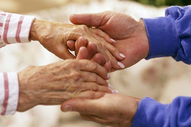 Man holding elderly woman's hands