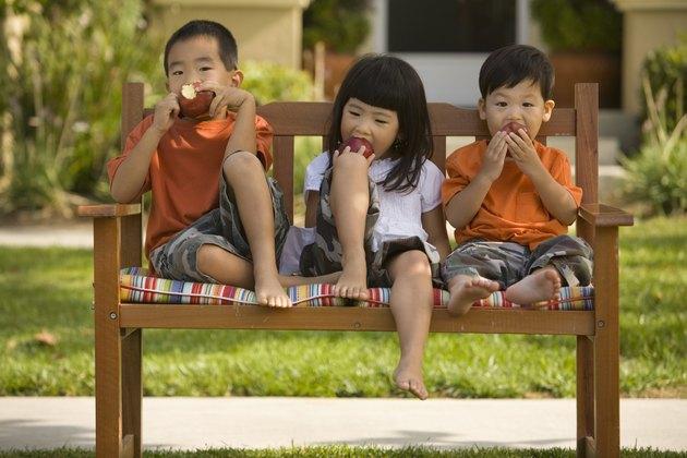 Asian siblings eating apples on bench